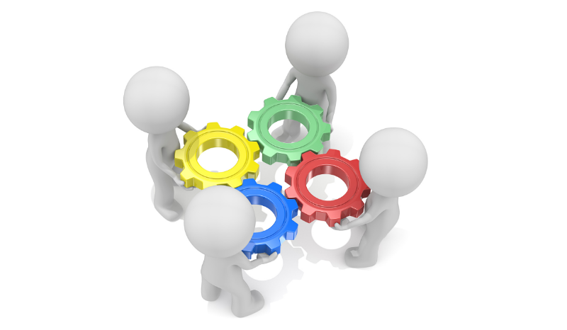Image of 4 people collaborating with colored gears