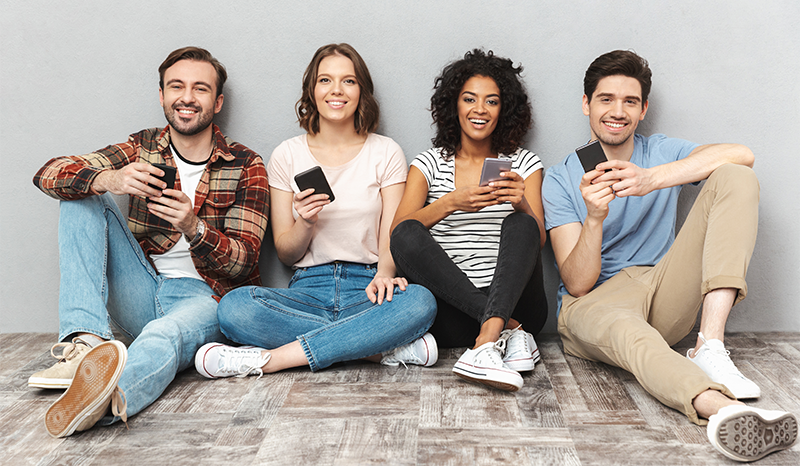 An image of 4 college students chatting, holding their mobile phone